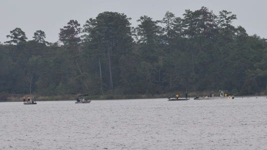 Divers search waters at Indian Creek Recreation Area on Saturday for a missing swimmer.