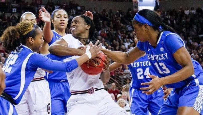 South Carolina's Doniyah Cliney grapples for the ball between Kentucky's Jaida Roper (32) and Evelyn Akhator.