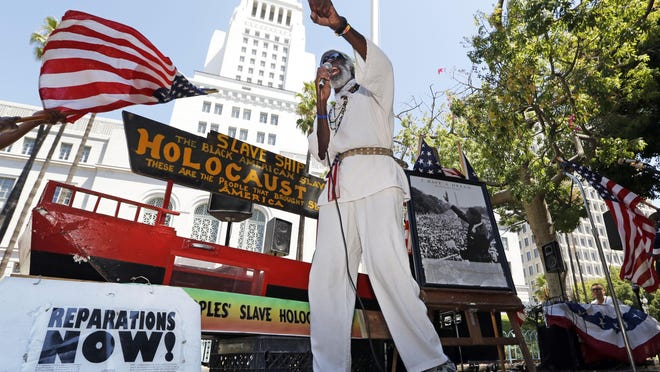 Los Angeles activist Ted Hayes stands with a scale model of a slave ship, in which thousands of slaves were brought to North America, during a rally to commemorate the 50th anniversary of the March On Washington, at Los Angeles City Hall in 2013.