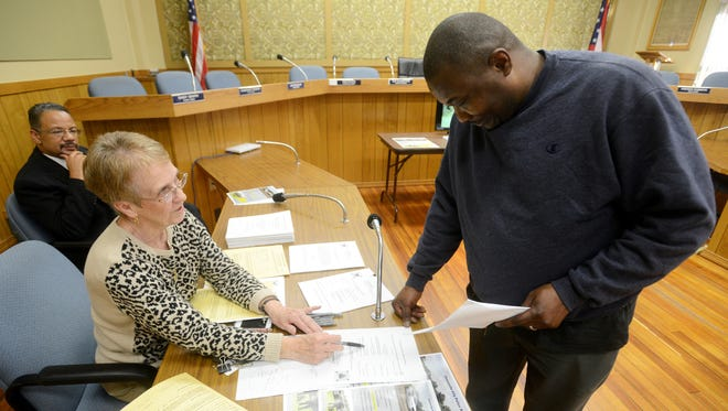 City of Zanesville Civil Service Employment Coordinator Virginia Hanifan talks to Shoin McBride as McBride submits his application for the Zanesville Police Department during a civil service job fair at Zanesville City Hall on Wednesday.
