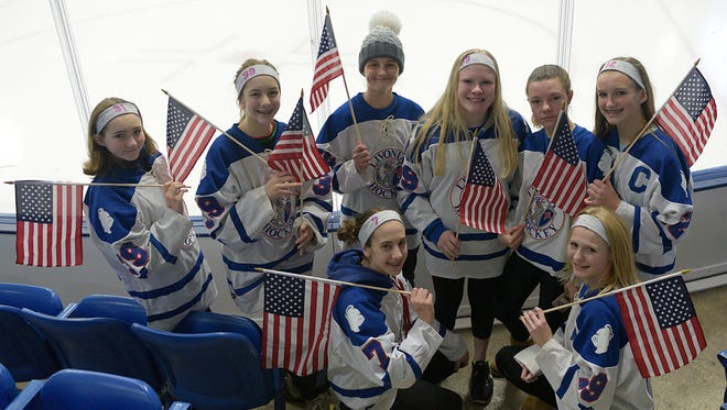 Players from the Livonia Knights 14-and-Under girls hockey team anticipate Saturday's game. Each fan in attendance received a miniature American flag to wave during the action.