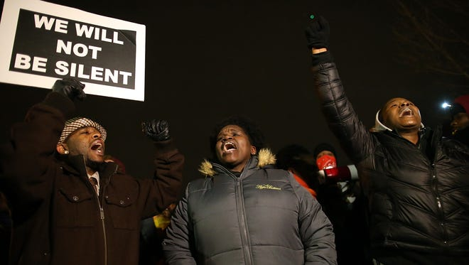 People protest in front of the Ferguson Police Department  on Monday.