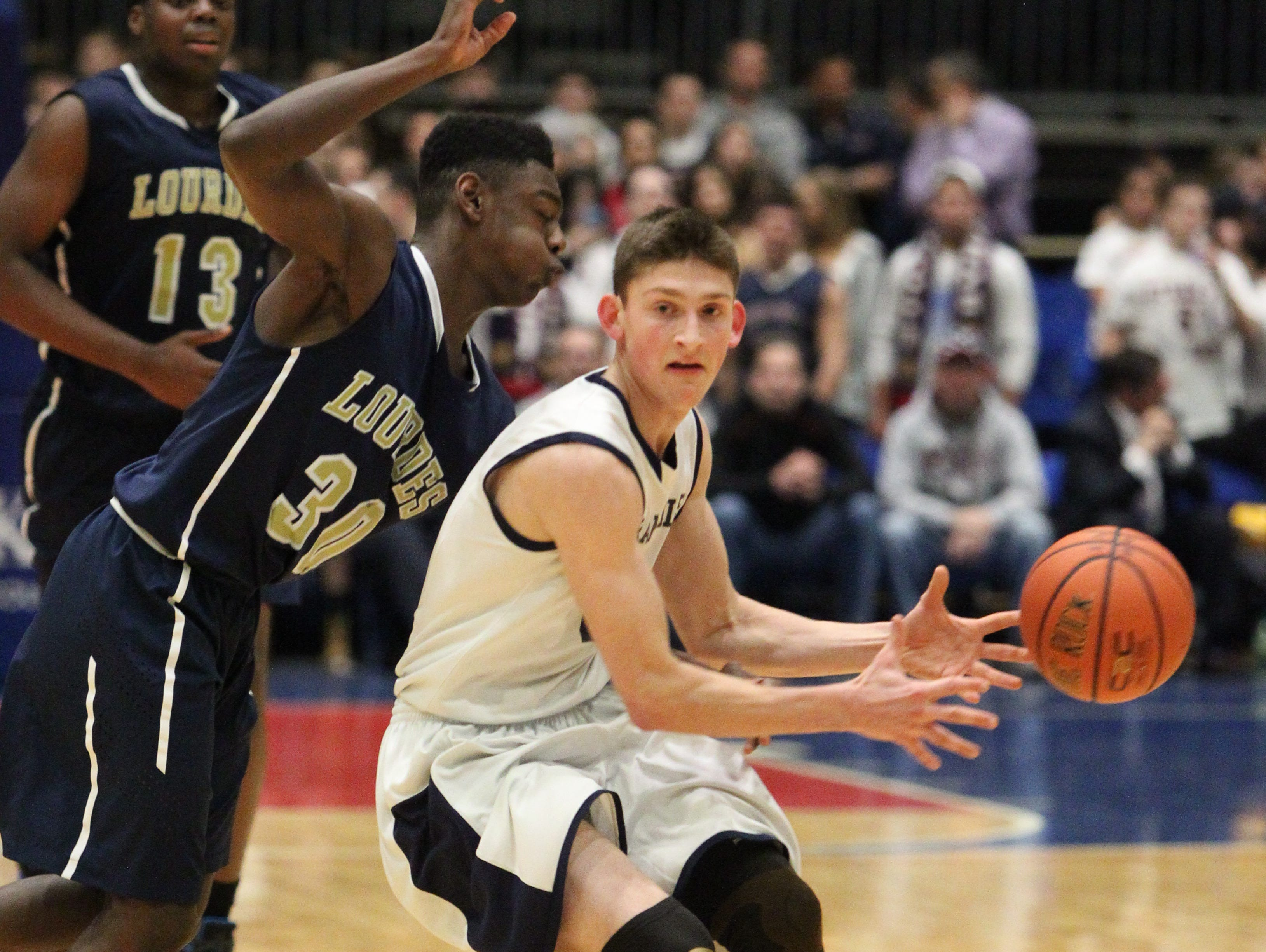Byram Hills' Jared Friedberg is pressured by Lourdes' Kevin Townes during their Section 1 Class A semifinal at the Westchester County Center Feb. 22, 2016.