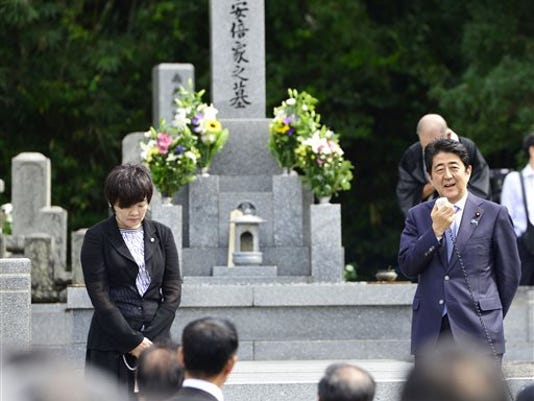 Japanese Prime Minister Shinzo Abe, right, accompanied by his wife, Akie, speaks to his supporters as he pays a visit to his ancestors' grave in Nagato, western Japan, Friday, Aug. 14, 2015.