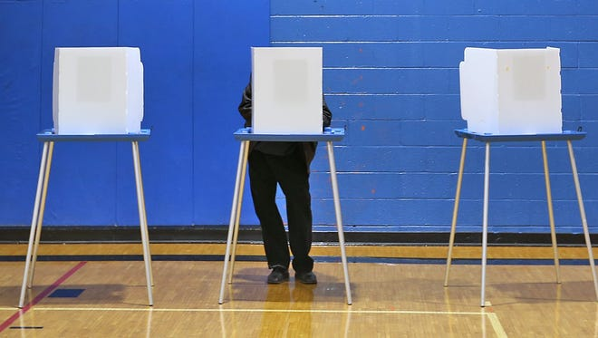 """A voter is shown casting his ballot on Election Day in 2014. Some Hamilton County Republican Party members are concerned that the party's leadership are acting like """"kingmakers"""" behind the scenes by favoring some primary candidates over others."""
