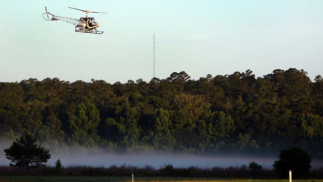 A helicopter flies low over a foggy greenway space while treating portions of both the Miccosukee Greenway and the Alford Greenway for fire ants through aerial distribution  in 2013.