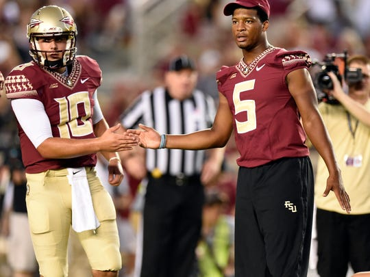 Sep 20, 2014; Tallahassee, FL, USA;  Florida State Seminoles quarterback Sean Maguire (10) shakes hands with quarterback Jameis Winston (5) who returned to the field after warming up in pads during pre game before their game against the Clemson Tigers at Doak Campbell Stadium. Winston was suspended for Saturday's game against Clemson pending an investigation into some alleged lewd comments he made on campus. Mandatory Credit: John David Mercer-USA TODAY Sports