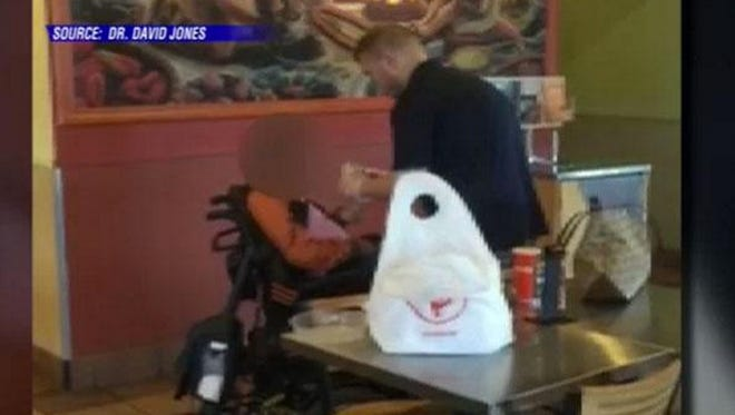 A Qdoba employee helps a disabled woman eat her burrito in Louisville.