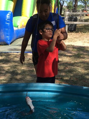 A camper, his buddy close behind, catches a fish from a tank at the 41st annual West Texas Rehab Center's summer camp.