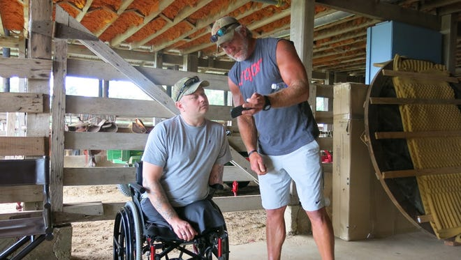 Retired NFL quarterback Brett Favre, right, and U.S. Army veteran Rusty Dunagan trade hunting stories and photos inside a barn at the Lauderdale County, Miss., farm of actress Sela Ward on Monday, June 9, 2014.  (AP Photo/The Meridian Star, Terri Ferguson Smith )