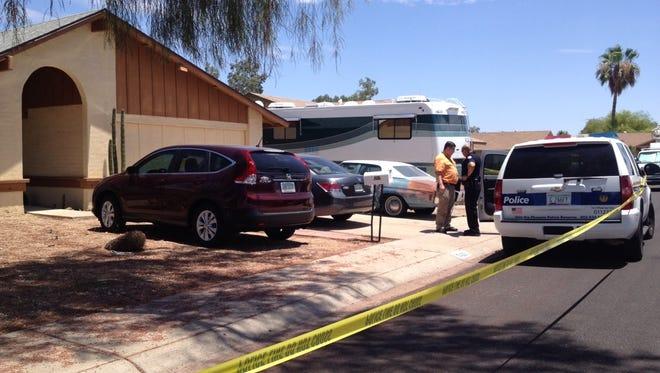Investigators gather outside the scene at the home in north Phoenix.