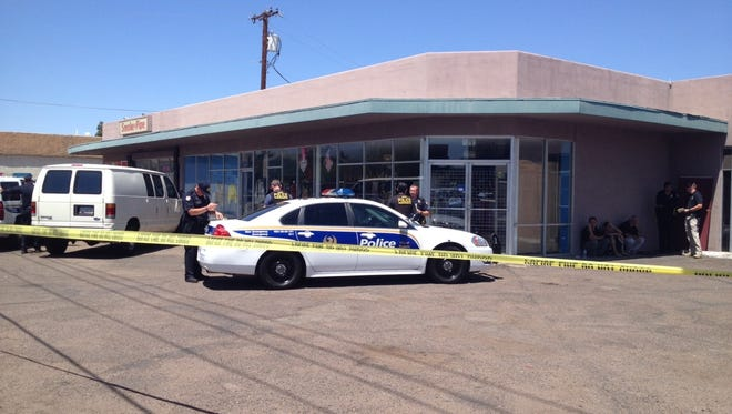 Officers outside the smoke shop in Phoenix where a body was found on April 29, 2014.
