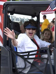 Patriotic parade rider Shirley Cherney of Little Sturgeon gives an enthusiastic greeting along the Belgian Days route last year.