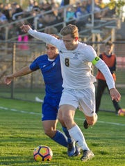Hartland's Brady Walker (right), who scored his 20th goal of the season in the first half, battles Lakeland's Cody Tiedeman for the ball in a district soccer game Tuesday night.