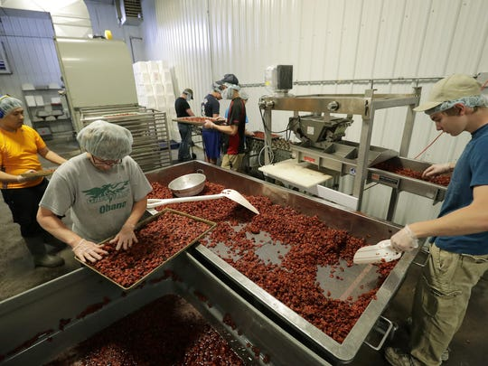 Phyllis Van Asten, bottom left, of Wrightstown and Jake Hennessey, right, of Little Chute put cherries on a pan to dry at Cherryland's Best in Little Chute.