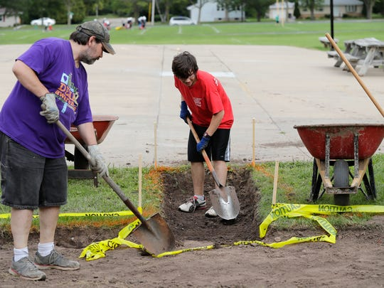 Appleton East High School student Trebor Rusch, 16, prepares the site for a labyrinth at Madison Middle School on Friday, August 26, 2016 in Appleton, Wisconsin. Trebor is installing the labyrinth to earn his Boy Scout Eagle rank. At left is Trebor's father Robert Rusch.