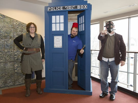 "Meredith Meier as ""River Song,"" Justin Schnell as ""the Doctor"" and Jason Kunde as the ""Empty Child"" pose in front of the TARDIS Tuesday, Dec. 6, at Manitowoc Public Library."