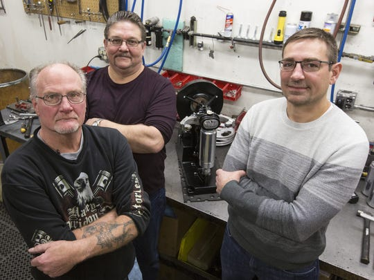 Dave Ebert, John Henfer and Joel Andrew around their automatic canning machine made by Wisconsin Aluminum Foundry in Manitowoc that seals the 32-ounce cans of beer known as crowlers.