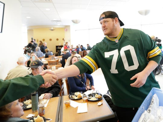 Green Bay Packers guard T.J. Lang (70) shakes the hand of a veteran at the Milo C. Huempfner VA Community Based Outpatient Clinic on Tuesday, November 8, 2016, in Green Bay, Wis. As part of Packers Give Back, the players visited patients at the facility as well as serving lunch and delivering gifts.
