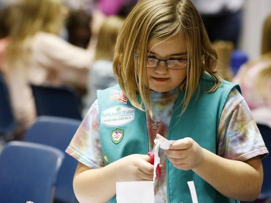 Skye Boettcher, 9, of Girl Scout troop 8173 works on