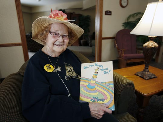 FILE - Sally Semmes, who started the Hatrack Storytellers more than 50 years ago, shows off one of her hats and a very popular children's book.