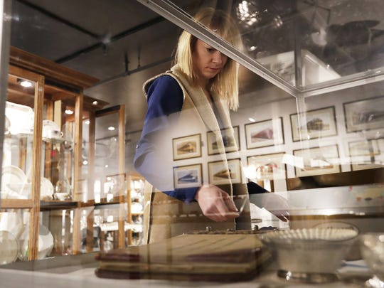 Erika Lusthoff, curator of the Jay W. Christopher Transportation China Collection, arranges a display case for the new exhibit at the National Railroad Museum in Ashwaubenon on Tuesday. The exhibit, featuring travel-themed china and other dining pieces from the collection of Jay Christopher of Sheboygan, opens Saturday.