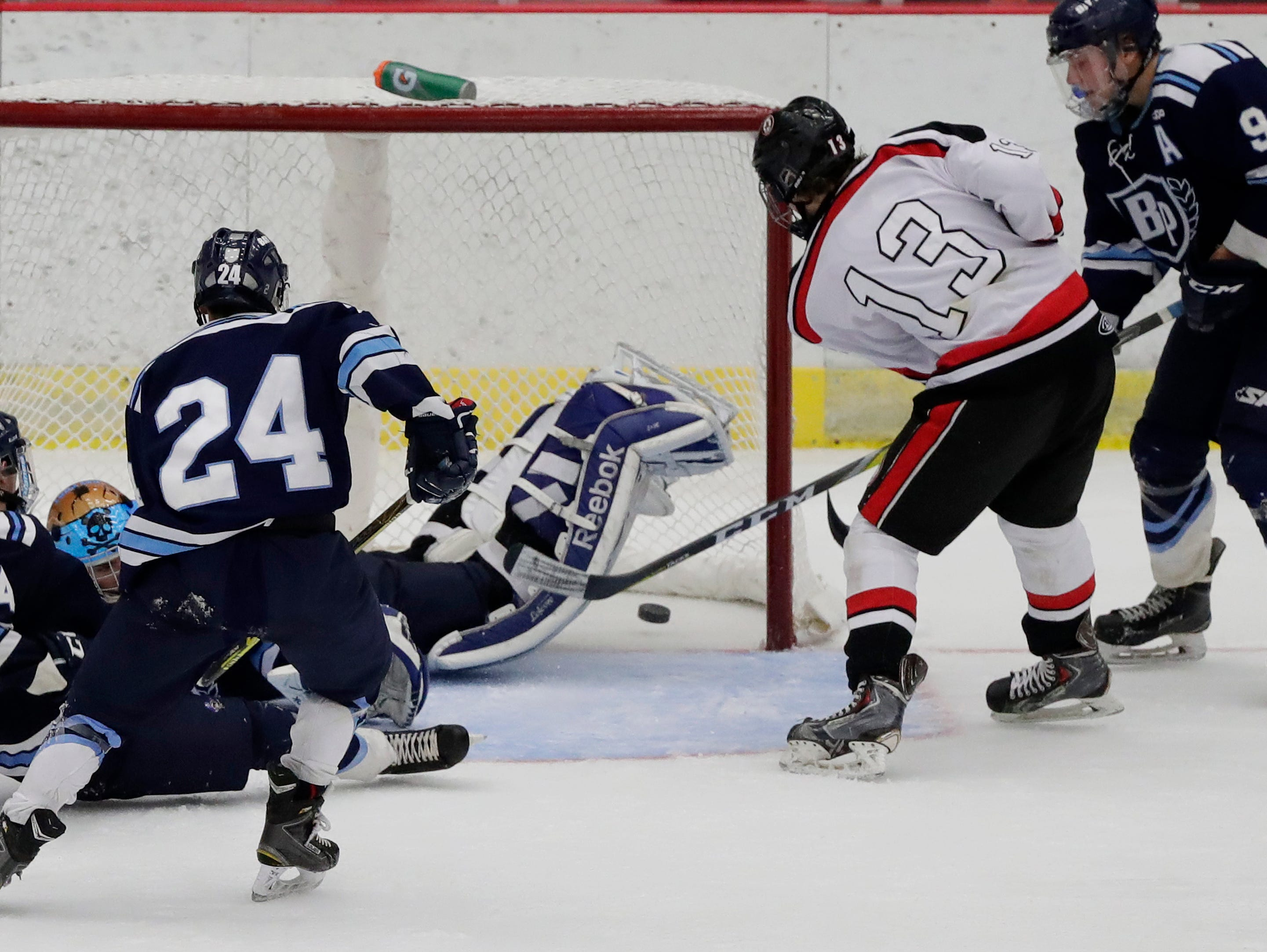 Sun Prairie Cardinals forward Josh McCrary (13) scores against the Bay Port Pirates to give the Cardinals a 3-2 lead with 14.1 seconds left in a quarterfinal match at the WIAA state hockey tournament at the Alliant Energy Center in Madison.