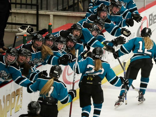 Bay Area Ice Bears players celebrate with forward Abby Anderson (12) after she scored to tie the game 1-1 against the Hayward Hurricanes in a WIAA state girls hockey semifinal game Friday at the Alliant Energy Center in Madison.