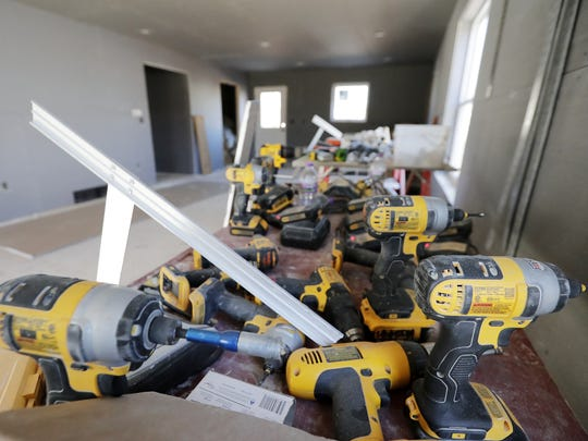 A table of drills is shown inside a house under construction