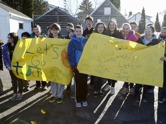 St. Francis of Assisi middle school kids hold up signs