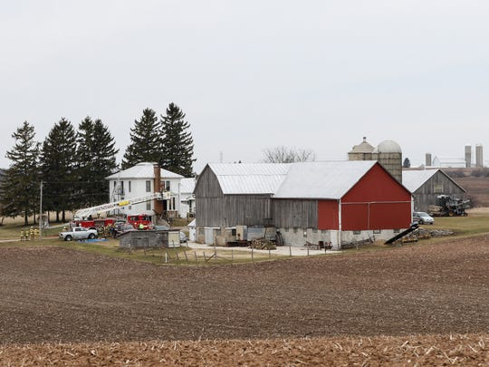Firefighters work to put out remnants of a fire at 13016 Morgan Road in Reedsville March 29.