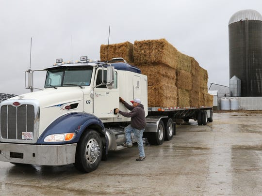 Paul Litz gets into his truck loaded with more than 30 bales of alfalfa hay, which he will drive to a Kansas ranch in need.