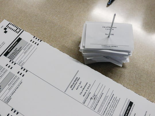 1,190 voter receipts lay next to a ballot in Manitowoc's