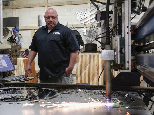 Shane Henderson, Metal Art of Wisconsin owner, watches