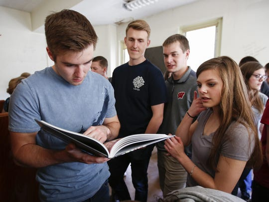 From left, Mychael Dopirak, Alex Wideman, Brett Bouc and Alyssa Kliment look through the old yearbooks in the room that used to house the yearbook club in Manitowoc Lincoln High School's tower Thursday.