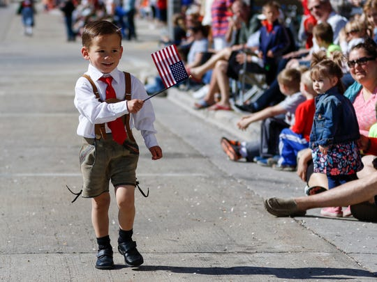 Micah Cerkas, 3, of Reedsville, plays up the crowd as he marches in Manitowoc's Memorial Day parade Monday, May 29, 2017, in Manitowoc, Wis.