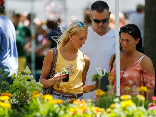 FILE - Miranda Tarpinian, left, looks at succulents with her parents TJ and Tina Tarpinian at the Garden Faire at Washington Park in 2017.