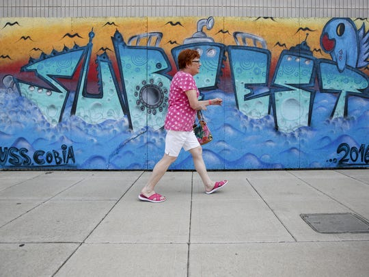 A woman walks by some Subfest art from 2016 during this year's opening day Friday in Manitowoc.