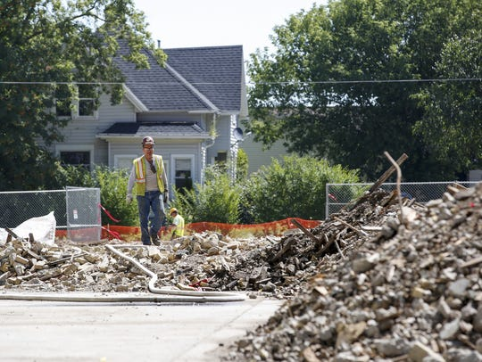 A construction worker walks over the rubble where a