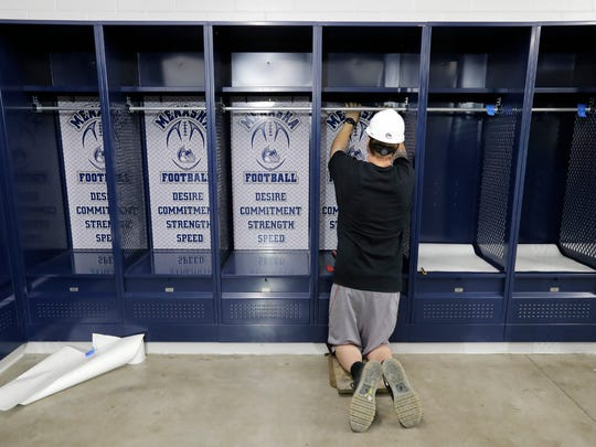 Alex Cropsey, an employee with Envisionink Printing Solutions, installs locker room graphics at Calder Stadium Monday.