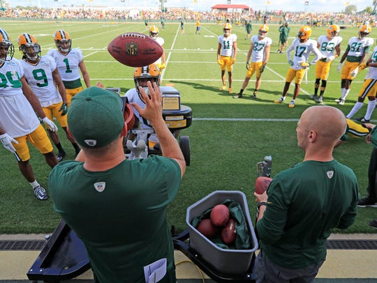 Green Bay Packers players participate in ball drills