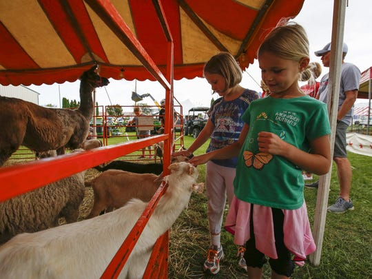 Ava Danford, 6, right, pets a baby goat at the kids'