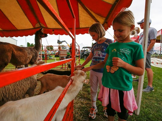 Ava Danford, 6, right, pets a baby goat at the kids petting area at the Manitowoc County Fair Wednesday, Aug. 23, 2017, in Manitowoc, Wis. Josh Clark/USA TODAY NETWORK-Wisconsin