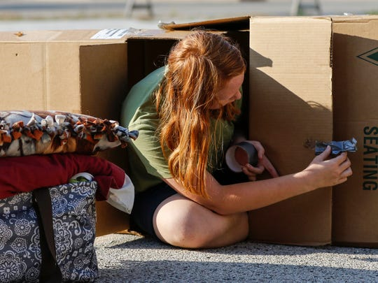 File - Idella Robley creates a door to her temporary shelter at Cardboard City in The Haven parking lot Sept. 23, 2017, in Manitowoc.