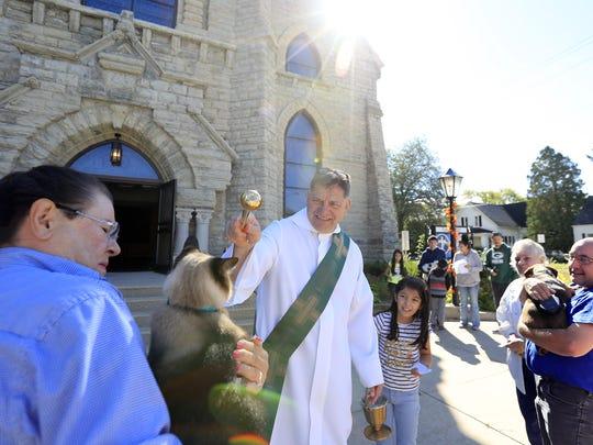 Deacon Paul Umentum sprinkles holy water on Irene Mayer's
