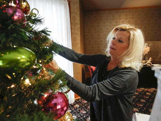 """File - Paula Feest places ornaments on her display for """"Christmas in the Mansion"""" at the Rahr-West Museum in 2017."""