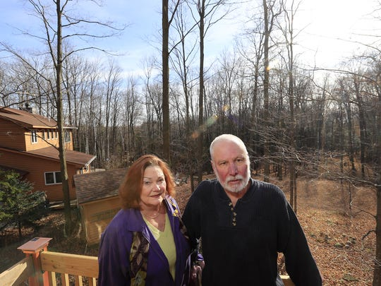 Deb and Scott Kliment stand outside their home in the