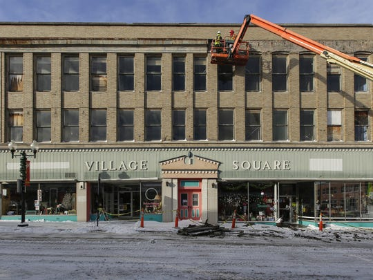 FILE - Crews work to repair damage to the Village Square building Dec. 14, 2017, in downtown Manitowoc. High winds and heavy snowfall brought down parts of the building.