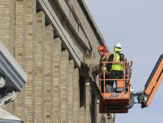 A city crew works to repair damage to the Village Square