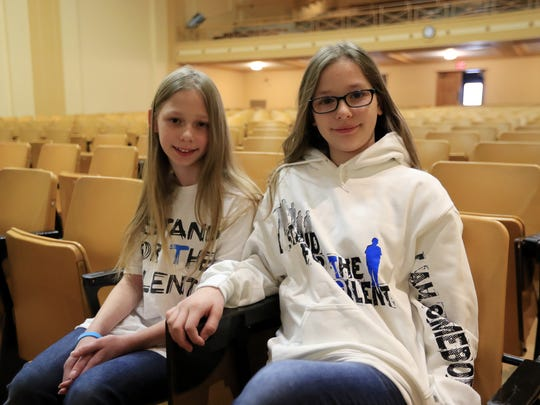 Ten-year-old Wilder Elementary students Ireland and Isabella Kirkpatrick sit in the auditorium before participating in an anti-bullying presentation at Washington Middle School on Monday in Green Bay. The girls raised $2,500 from a lemonade stand and other fundraising efforts to bring the anti-bullying program to Green Bay.